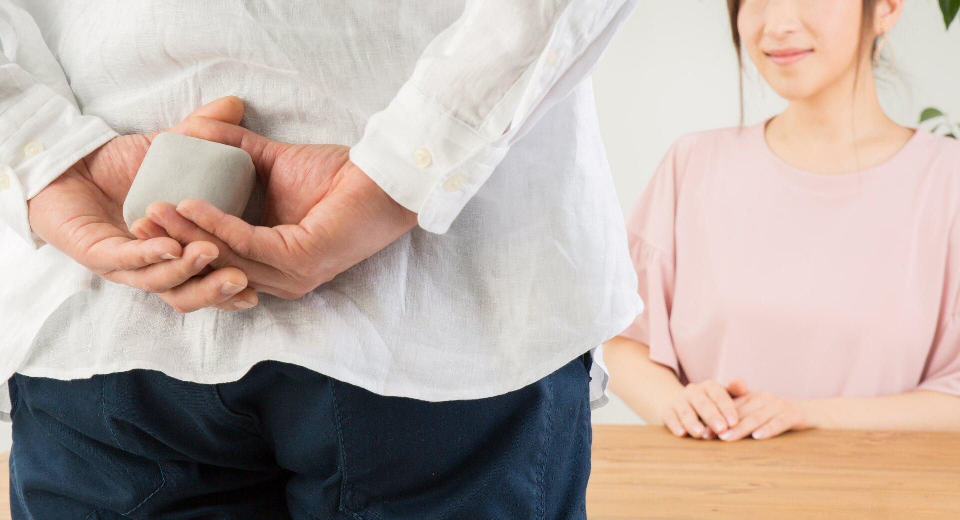 女性に告白しようとしている男性の写真。指輪を後ろ手に隠し持っている。