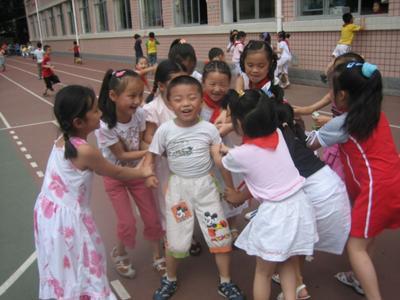 女の子に囲まれている坊主頭の少年の写真