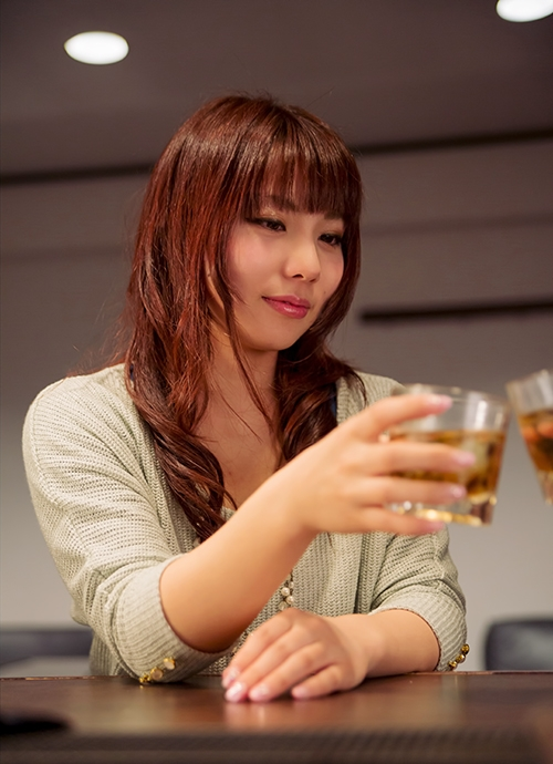 ウイスキーのグラスを飲もうとする女性の画像
