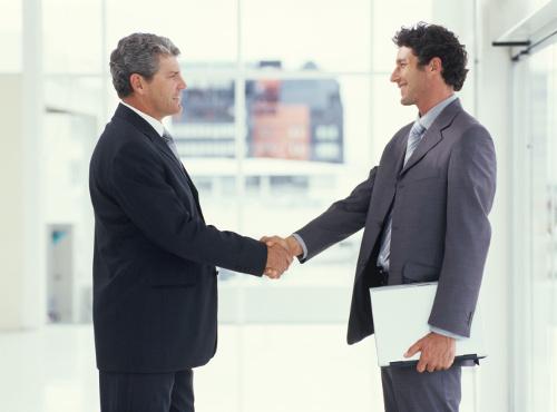 ビジネスシーンであいさつしている2人の外国人の画像
