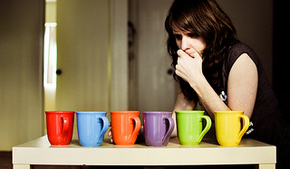 たくさんの色のコップの前に立って、どれを選ぼうか迷っている外国人女性の画像