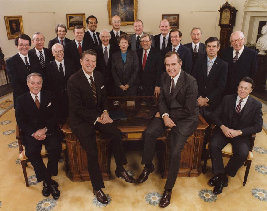 大きな板の机に腰掛ける複数人のスーツを着たアメリカ人の画像