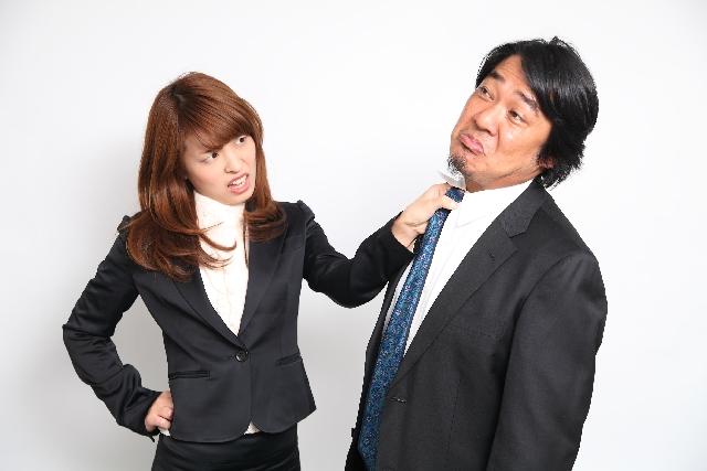 女性社員が男性社員のネクタイを掴んでいる画像