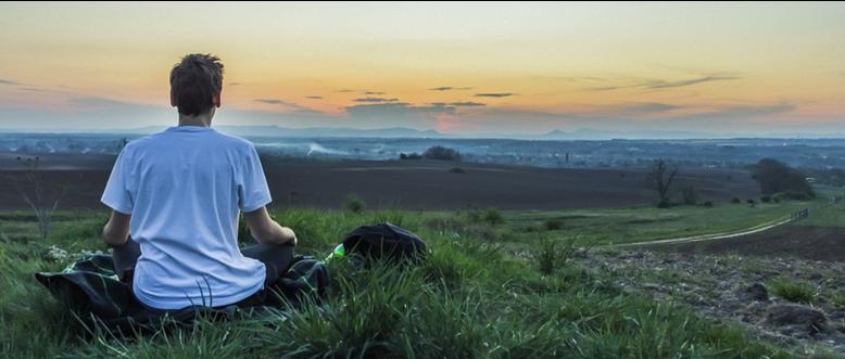 草原で瞑想している男性の画像