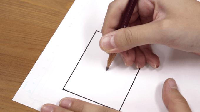 消失点を決めるために鉛筆でコマの中央に印をつけているところの画像