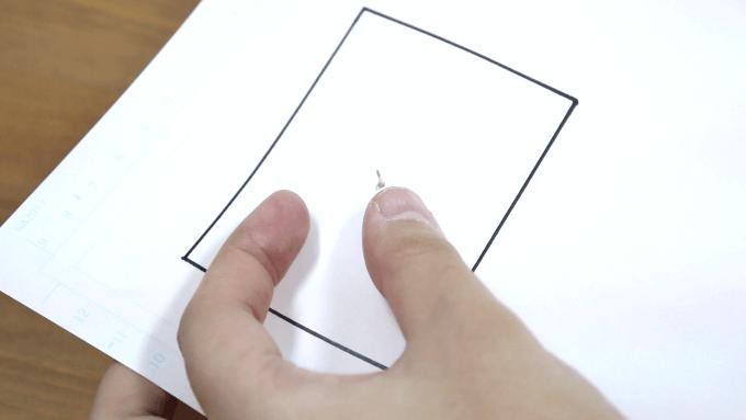 紙に画鋲を刺しているところの画像